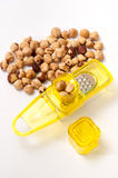 Small yellow grater with a bunch of hazelnuts Stock Image