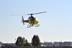 The small yellow helicopter flies in the sky over the city. Royalty Free Stock Photo