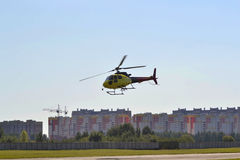 The small yellow helicopter flies in the sky over the city. The small yellow helicopter flies in the sky Royalty Free Stock Images
