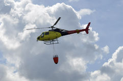 The small yellow helicopter in the sky. Stock Photo