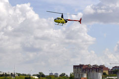 The small yellow helicopter in the sky. Stock Photos