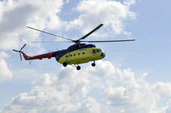 The small yellow helicopter in the sky. Stock Images