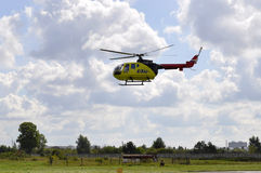The small yellow helicopter of Utair airline in the sky. Stock Image