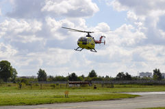 The small yellow helicopter of Utair airline in the sky. Royalty Free Stock Photo