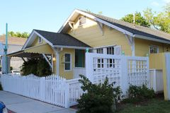 A small yellow house with white fence. A small cozy house with a white fence and green bushes in the summer, Amelia island, Florida, USA royalty free stock image