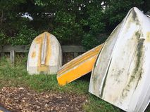 Small yellow metal boats or dinghies leaning against wooden fence Stock Image