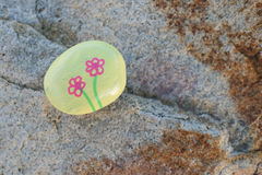 Small yellow painted rock on a boulder Stock Photo
