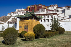 A small yellow pavilion with a green roof and a decorative bush in front of the Potala Palace in Lhasa Stock Photo