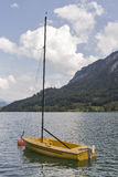 Small yellow sailing yacht on Alpine lake Mondsee in Austria stock photography