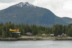 Small yellow seaplane flying over and landing in the small city Royalty Free Stock Image