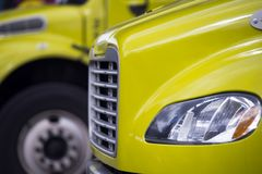 Part of semi truck cab with grille headlight and fender with ano. Small yellow semi truck with box trailer and refrigeration unit for local delivery of cooled Royalty Free Stock Photos