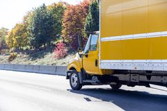 Small yellow semi truck for moving local cargo with box trailer. Yellow small size compact rig semi truck with box trailer transporting local commercial cargo royalty free stock photo