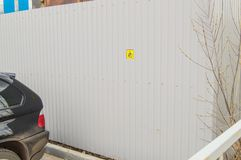 Small yellow sign on a metal fence informing about Parking for disabled people, poor awareness, poor organization of Parking for. Disabled people in Parking lot royalty free stock image