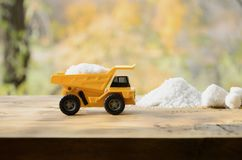 A small yellow toy truck is loaded with a stone of white salt ne