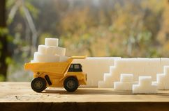 A small yellow toy truck is loaded with white sugar cubes near t