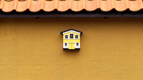 Small yellow and white birdhouse on a yellow wall Stock Photography