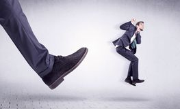 Young worker kicked out by big foot. Small young businessman kicked out by a big black shoe Royalty Free Stock Photos