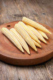 Small young corn cobs. Pile of small young corn cobs on the wooden background  close up Royalty Free Stock Image