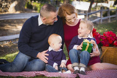 Small Young Family Opening Christmas Gifts in the Park Stock Images