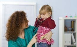 Small young girl at doctor trying on stethoscope Royalty Free Stock Image