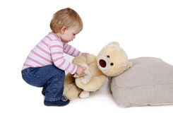 Small young girl lies down Teddybear Stock Photo