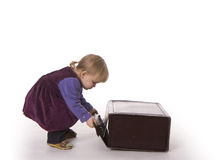 Small young girl raises big suitcase Royalty Free Stock Images