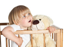Small young girl standing in cot hugging Teddybear Royalty Free Stock Images