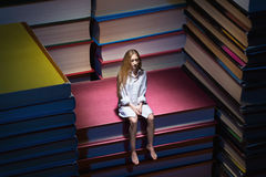 Small young woman sitting on books Royalty Free Stock Photography