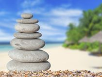 Small zen stone with beautiful sand and palm tree beach background. For spa and balance symbol Stock Images