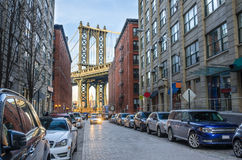 Smalle Cobbled-Straat met de Brug van Manhattan op Achtergrond stock foto's