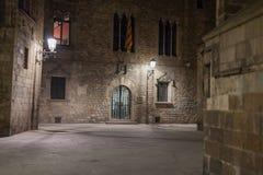 Smalle die steeg door straatlantaarns bij nacht wordt verlicht Stock Foto's
