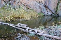 Smalle oude houten brug over kleine rivier Stock Foto