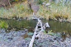 Smalle oude houten brug over kleine rivier Stock Afbeeldingen