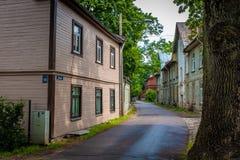 Smalle straat in de voorsteden met traditionele houten rijtjeshuizen in Riga stock fotografie
