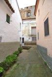 Smalle straat in een kleine stad met kasteel bij Stock Foto's
