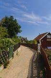 Smalle straat en rode plattelandshuisjes in Zweden Stock Foto's