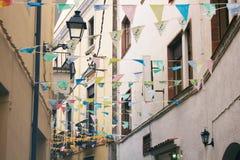 Smalle straat met gele voorgevels van huizen, lantaarn en decoratieve vlaggen in historisch district van Spaanse stad Stock Fotografie