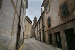 Smalle straat onder oude gebouwen Stock Afbeeldingen