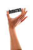 Smaller democracy concept. Color vertical shot of a of a hand squeezing the word 'democracy royalty free stock photos