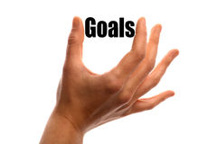 Smaller goals. Horizontal shot of a hand squeezing the word Goals between two fingers, isolated on white Stock Photo
