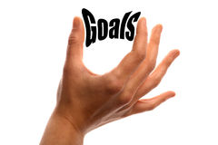 Smaller goals. Vertical shot of a hand squeezing the word Goals between two fingers, isolated on white Royalty Free Stock Photos