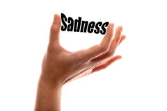 Smaller sadness. Color horizontal shot of a of a hand squeezing the word sadness Royalty Free Stock Images