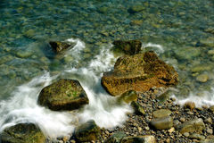 Smaller waves curl around and wash over large boulders covered w Royalty Free Stock Photo