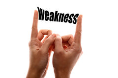 Smaller weakness. Color horizontal shot of a two hands squeezing the word weakness Stock Photos