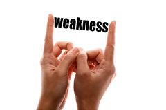 Smaller weakness. Color horizontal shot of a two hands squeezing the word weakness Stock Image