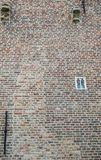 Smallest window of Europe is in Bruges, Flanders, Belgium. Bruges, Flanders, Belgium -  June 17, 2019: Smallest window of Europe is set in brown-gray brick wall royalty free stock images