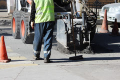 Smantellamento della pavimentazione dell'asfalto sulla strada mentre guidando le macchine per mezzo di mini idro-martello mentre  Fotografie Stock