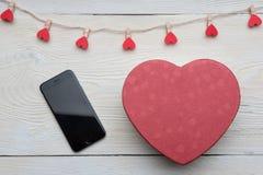 Smarphone e coração vermelho no fundo de madeira branco fotos de stock