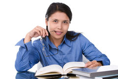Smart. An educated young female (student or teacher) bite the tip of her glasses when she read the book on the glass desk Royalty Free Stock Images