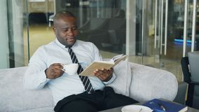 Smart African American businessman in formal clothes reading book while drinking coffee in glassy cafe at lunch break stock footage